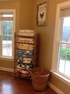 French and American quilts and an antique rolling shoe rack .  French pickers basket to the side.