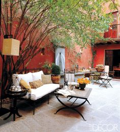 The two-story house owned by interior designer Leslie Tung and architect Gerard McCormack in the Mexican town of San Miguel de Allende features a tile-floored courtyard garden. The settee is by Casamidy, and the checkerboard stone-and-marble table was designed by Lis Bisgaard for Tung's shop, Mitu Atelier. The red walls were inspired by the colors of China's Forbidden City; landscape architect Alfonso Alarcon fashioned the cement fountain.