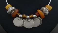 by Christopher William | Necklace; Ancient beads of Tibetan yellow Amber with old tribal Silver discs and fluted beads from north India, on a Sterling Silver cable chain. The resin spacers between the discs are from an old Naga piece.  {SOLD ~ 220$}