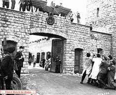 Mauthausen-Following the liberation, freed prisoners pull down the eagle and swastika insignia from above the main entrance gate. The iron bars that once supported the eagle and swastika still remain above the main gate.