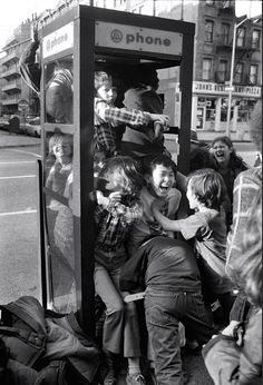 New York, 1975 by Meyer Liebowitz. | vintage | phone booth | children playing | messing around | squashed | black & white photography | NYC | 1970's | fun | kids | laughter | squish