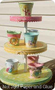 How I would make this: Lids from different size tins (cookie, etc.) - paint; use decorative paper for center of each tier (cut in scallops); use same paper as center (with smaller scallops) to trim edges of lids