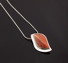 Goldstone cabochon in a handmade sterling silver setting.