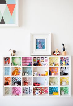 DIY kids room shelving splash of color - transform plain kids shelves with scrapbooking paper, old birthday cards, anything to give a terrific backdrop for shelving.