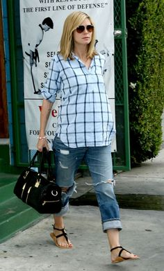 Slouchy boyfriend jeans can work during pregnancy. Make sure the top you choose has a subtle empire waist like Heidi Klum's plaid shirt to emphasize the narrowest part of your body and avoid looking heavy all over.