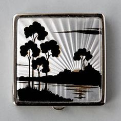 A small square chrome-plated compact for loose powder. The scene on the lid is really beautiful. The delicate sun ray patterns in the foil are lovely when turned in the light