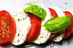 Tomato and mozzarella salad with fresh basil leaves black pepper