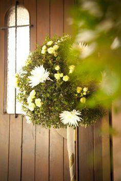 Decoración de entrada de iglesia con arboles de boj decorados con rosas racimo y crisantemos blancos.