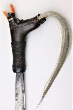 Mandau / Parang Ilang - Dayak - Borneo - Indonesië  Eertijds waren de Dayak van Centraal-Borneo berucht als koppensnellers waarbij de mandau het wapen was dat in het gevecht werd gebruikt.Het lemmet is hol / bol geslepen voor een effectievere slag schuin van rechtsboven naar linksonder.De greep heeft ingesneden versieringen en is versierd met witte en gekleurde plukjes geitenhaar.De schede is gedecoreerd met fijn snijwerk.Aan de schedemond ontbreekt een klein stukje hout (zie foto).De mandau…
