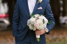 Groom in Navy Blue Suit with Blush Pink Pocket Square and White Rose Boutonnière, holding Blush and Ivory Rose with White Hydrangea and Greenery Bouquet