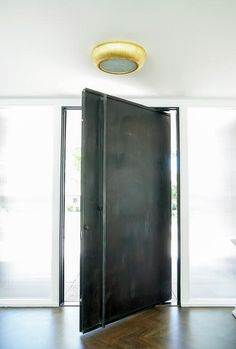 A brushed gold flush mount lights a black metal pivot front door complemented with a wood herringbone pattern floor. Industrial Front Doors, Wood Front Doors, Modern Front Door, Front Door Entrance, House Front Door, Metal Doors, Black Entry Doors, Black Door, Pivot Doors