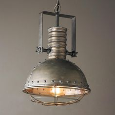 """Industrial Caged Pendant with Rivots Featuring industrial style rivets and a caged lamp face, this chic pendant has rugged style with vintage appeal. An aged steel finish with both pewter and bronze overtones works well in your kitchen, work space or bar area.1-40watt max medium base bulb. 42"""" matching chain and 5"""" round canopy included. (18""""Hx13""""W)"""