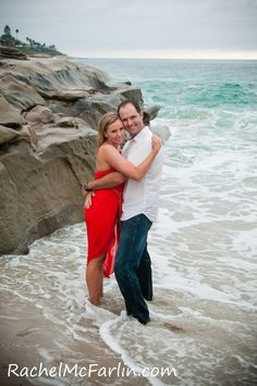 Creative Romantic Engagement Photo on the beach at sunset with rocks - couple standing in the waves and surf  - destination wedding style in La Jolla San Diego    www.rachelmcfarlinphotography.com Rachel McFarlin Photography