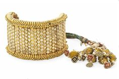 A DIAMOND-SET GOLD BRACELET INDIA, 19TH CENTURY The gold mounts articulated along a braided cord, predominantly with table-cut diamonds, the sides with foiled emeralds, the ties of green and red fabrics with tassels Not including tassels 7½in. (19cm.) long