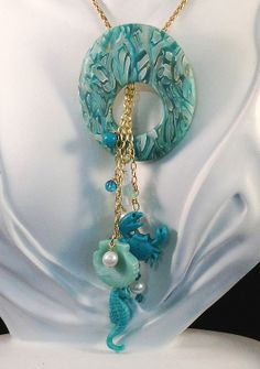 LadyFlowersbySusan Seaside Vacation, Polymer Clay  This pendant is made from one of my signature translucent Stroppel canes. A tiny armature on the back suspends three chains dotted with polymer sea creatures, pearls, Swarovski beads, jade beads and turquoise beads. This pendant won second place in the August Polymer Clay Central Challenge. (2013).