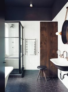 A rustic and moody bathroom with a black ceiling and dark wood features