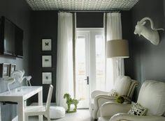 Black walls and trellis patterned ceiling, plus stark white drapes