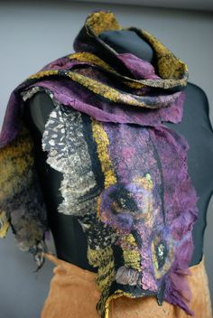 This scarf is made out of a a piece of hand dyed silk gauze on the bottom and pieces of multi colored china silk and silk gauze on top with a very thin layer of black merino wool in the middle. There are also quite a few ruffles along the edges. The technique is called nuno Felting or laminating wool and silk after many hours of working the fibers you get the end result which is a ruched effect but is light and airy since I use very little wool it drapes like pure silk! The result is a…