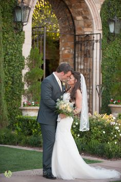 Bride and groom share a loving look- garden venue with lush green grounds and rustic large gate   Lasting Images Photography   villasiena.cc