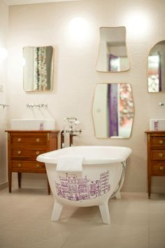 old bathtub with purple drawings and different shapes of mirrors