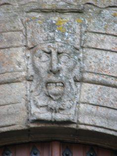 El mascarón con forma humana y expresión burlona que hace de clave en el arco de la entrada Norte de la iglesia de S Juan Bautista.