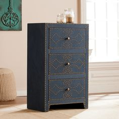 Just close your eyes and wiggle your toes in the sand, you can almost hear the seaside calling with this intricately detailed yet fantastically functional cabinet. Ornately edgy nailhead trim dances across the front while soft, navy toned linen and