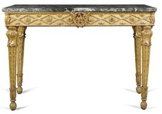 An Italian carved giltwood console table, Roman late 18th century with a rectangular veined white, grey and green marble top above a frieze centred by an eagle within a wreath flanked by diaper motif enclosed flowerheads on tapering acanthus and lotus leaf carved legs terminating in foliate carved ball feet; with a partly illegible  paper label to the back handwritten in ink ...Roma