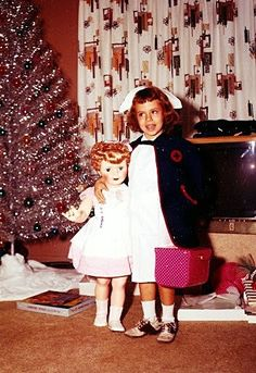 """Christmas 1962.  IN EVERY DETAIL this could be a picture of our house: the aluminum tree with monochromatic ornaments, the drapes, the panther TV light, the nurse outfit, the saddle oxfords, the """"walking-doll.""""  It's all there."""