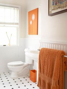 Orange + White - Give a white bathroom a shocking dose of color to add personality to an otherwise blank space. Accessories, linens, and artwork in a similar shade of orange pop against this bathroom's white surfaces. Fun extras such as these can give your bathroom a new look without breaking the bank or being a permanent addition, a major plus for renters.