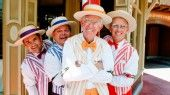 The Dapper Dans dressed in barbershop quartet outfits smile and pose for the camera