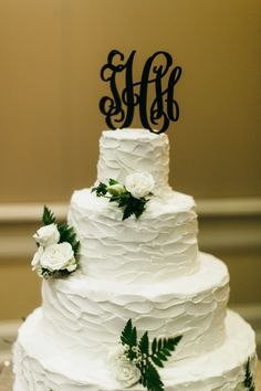 A black monogram cake topper makes a statement on this beautiful white cake.