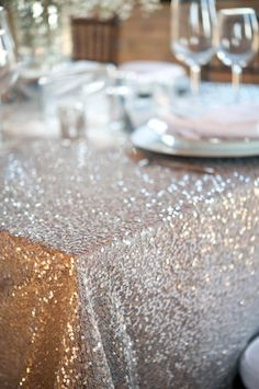 sequin table cloth. Oh man, this would be super amazing for the dessert table filled with metalic cakes and goodies like silver cotton candy, gold shards of rock candy, metalic wrapped buttercreme mints, etc. (With white or purple rock candy chandeliers overhead hehe)