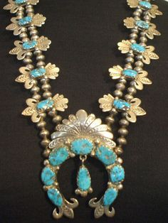 OLD NAVAJO SQUASH BLOSSOM NECKLACE DESCRIPTION: This exquisite squash blossom necklace dates from the 1930s to 1940s. It features 19 specimens of deep Blue Gem turquoise set in scalloped bezel. The sterling silver blossoms have a fleur-de-lis design, with loads of stamp-work and