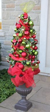 T'his is a Christmas Tree Topiary made with a Tomato Cage.  Pretty outside the front door.