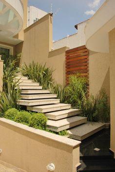 Entrada principal da residência e para emoldurar a escada e propor uma sensação dela estar flutuando entre a vegetação foi elaborado um jardim com baixa manutenção com Formóis, buxinhos, arundinas e um painel de madeira. Projeto de Lilia Toti.
