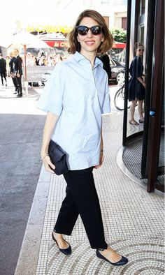 Sofia Coppola wears a blue collared blouse, black pants, oversized sunglasses, and black flats