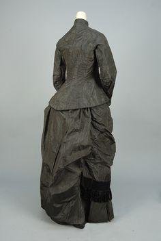 STRIPED SILK DAY DRESS, 1875 Black taffeta with white pinstripe trimmed in black satin, long boned bodice having buttons inlaid with mother of pearl flowers, ruched bustle skirt with self bows, satin band and silk fringe - whitakerauction