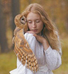 Russian photographer Katerina Plotnikova's amazing photo shows an owl perched on a young woman.