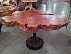 A custom side table made from a cross cut section of reclaimed lychee fruit wood tree and a salvaged steel base.  By Impact Imports of Boise and Philadelphia.