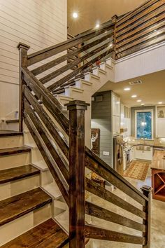 This blue farmhouse features a contemporary country design and includes reclaimed wood throughout the home. Board-and-batten paneling is used prominently, as are rustic design elements such as the wood stair rails and vaulted wood ceiling. #stairs #flights #walking #room
