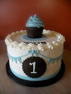 A cupcake on top of a birthday cake is a sweet idea. See more first boy birthday and party ideas at one-stop-party-ideas.com