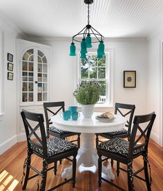 Beach-style dining room with captivating pops of turquoise