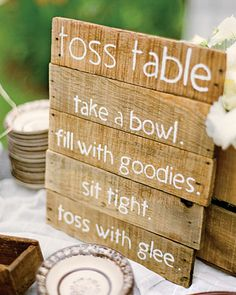 """Hand-painted pieces of wood from local fruit-market boxes served as signs for the """"toss table"""" and mojito bar."""