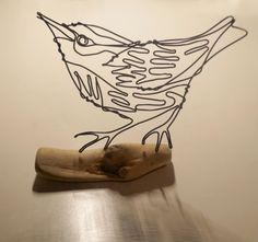 A beautiful, delicate wire sculpture of a life size Nuthatch bird mounted on driftwood, or as I like to call it, a drawing come to life.  Approx. 11.5cm wide 14cm high