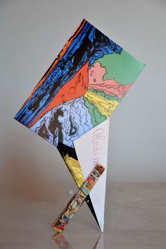 Photo-frame obtained by folding a sheet of recycled card so as to form the shape of a flattened inverted cone that sits stably thanks to a painted wooden clothes-peg. Designed by Riccardo Dalisi for the Museo Nazionale di Capodimonte, Naples.