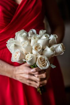 A bridesmaid in red holds a bouquet of simple white roses.