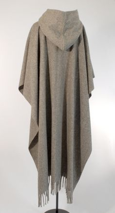 This open front poncho is classic and elegant due to the drape of the lightweight ironed wool. The ample hood and handmade cow horn buttons are beautiful details on this model. It is unisex and one si