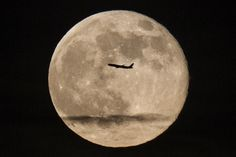 """A silhouetted airplane flies past a """"super moon"""" over New York on June 23, 2013."""