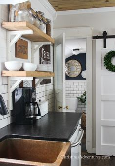 Farmhouse decor in the kitchen for spring and summer- this fixer upper   has come a long way!  Love the barn door and the copper sink