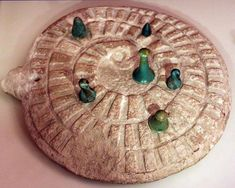 Mehen game with gamestones, from Abydos, Egypt. The first evidence of the game Mehen is as old as 3,000 BC. It was very popular during the Old Kingdom, and remained prevalent at least until the Third Intermediate Period. Mehen was played on a board which looks like a snail shell at first glance, but actually represents a snake. The most detailed playing pieces were shaped like lions. The set of pieces included about three to six game bits and a few small marbles.